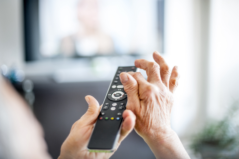 Senior woman at Golden West using remote control technology tools for older adults